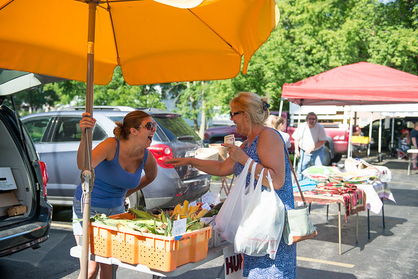 JOED VIERA/STAFF PHOTOGRAPHER-Newfane, NY- Diane Steel buys some corn, cucumbers and cherry from JoAnne Huntington at Huntington Farms booth during the Newfane Farmers Market.
