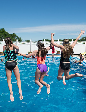 JOED VIERA/STAFF PHOTOGRAPHER-Lockport, NY-  Mia Rohde 12, Emma Beecher 12 and Clare Casalinuovo 12 jump in the Lockport Town and Country Club pool during Desales' Field Day.