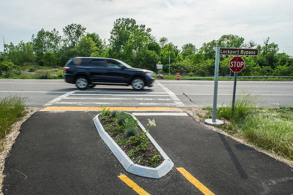 JOED VIERA/STAFF PHOTOGRAPHER-Lockport, NY- A car drives over the Lockport Bypass crosswalk on the Canal Bike Trail.