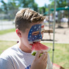 JOED VIERA/STAFF PHOTOGRAPHER-Lockport, NY-  Griffin Adams 10 eats a slice of watermelon after getting his face painted during Desales' Field Day.