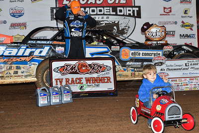 Blane Davenport posing victory lane as his dad Jonathan Davenport changes hats