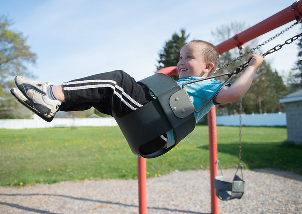 JOED VIERA/STAFF PHOTOGRAPHER-Lockport, NY-EJ Ubiles Jr. smiles on the swings at Dolan Park.
