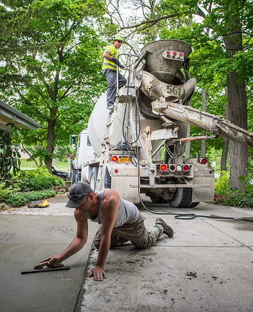 JOED VIERA/STAFF PHOTOGRAPHER-Lockport, NY-Jim McCullough and Steve Kazmiprczak lay down a concrete driveway in front of Jayette Sinclair's home on  Rydalmount Road.