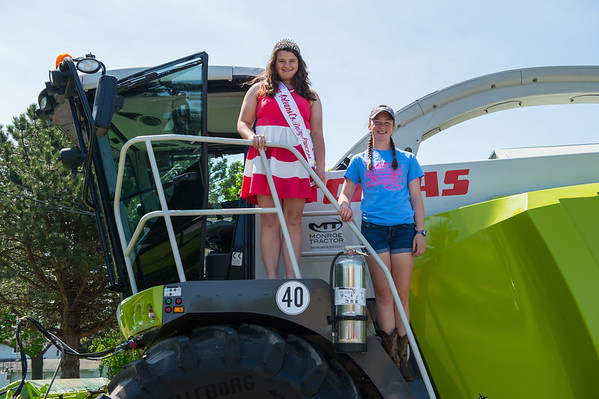 JOED VIERA/STAFF PHOTOGRAPHER-Barker, NY-Niagara/Orleans County Dairy Princess Allison Austin and Barker Future Farmers of America President Natalie Menz climb a tractor during an agriculture fair.
