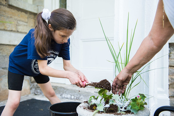 JOED VIERA/STAFF PHOTOGRAPHER-Lockport, NY-Emma Parada 8 helps her grandmother Toni Parada plant geraniums outside of Lockport Presbyterian Home