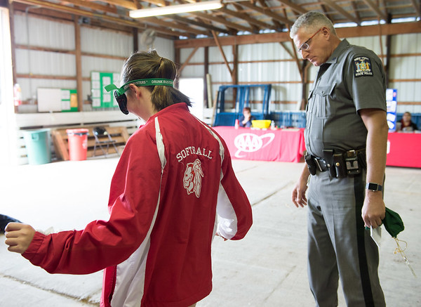 JOED VIERA/STAFF PHOTOGRAPHER-Lockport, NY-New York State Trooper Chris Pyc administers a sobriety test  on Bridget Wild as she wears drunk busters simulation goggles during the safety fair at the Niagara County Fairgrounds.