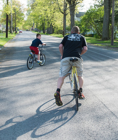 JOED VIERA/STAFF PHOTOGRAPHER-Lockport, NY-Zachary Smith and his nephew Jace Smith, 7, ride their bikes down Olcott Street after enjoying the swings at Dolan Park.