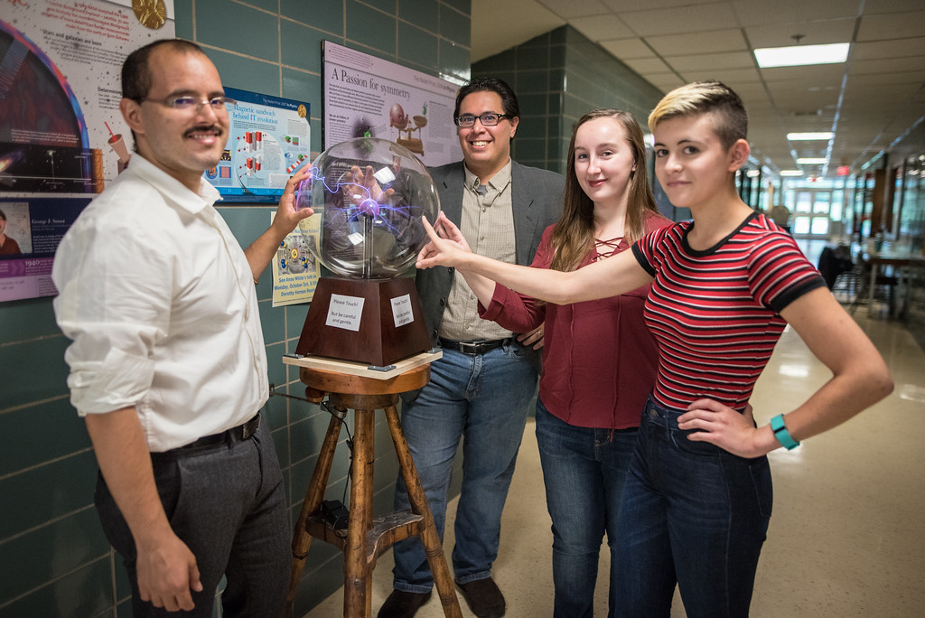 Carlos Cartagena, David Schaffner, Hayley Johnson and Codie Fiedler Kawaguchi around a plasma globe outside of David Schaffner's physics lab.