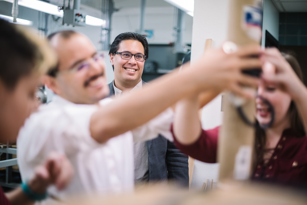 Codie Fiedler Kawaguchi, Carlos Cartagena, and Hayley Johnson in Professor David Schaffner's (center) physics lab.