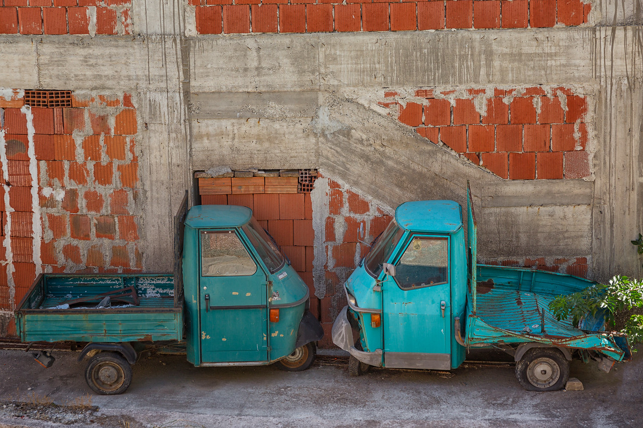 A pair of well-loved Piaggio Apes