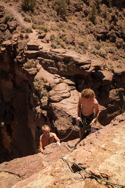 Noah belays Ezra up behind him from the summit of <i>The Pioneer Route 5.7 C0</i> on the Monkey Face Tower.