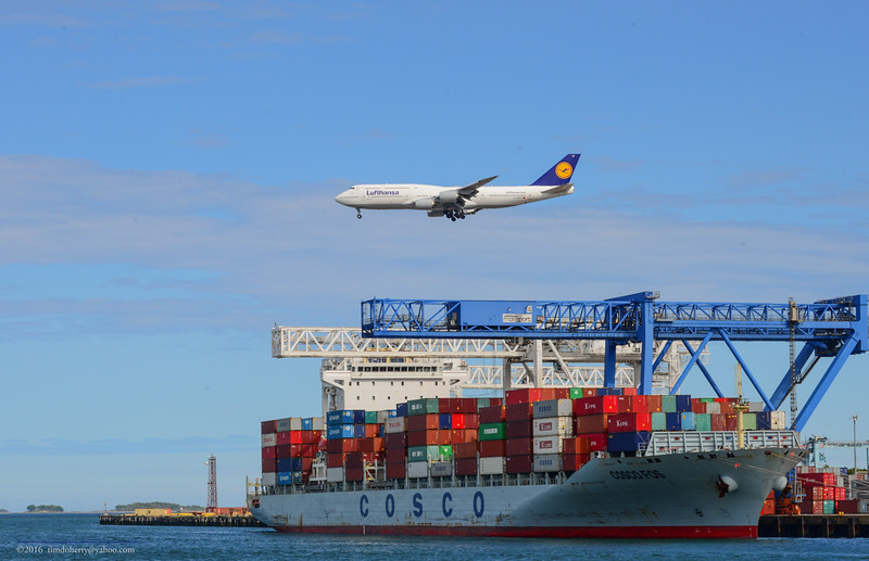On the afternoon of May 22, 2016 a Lufthansa 747-800 passes over the the Containership COSCO FOS at Conley Termial in South Boston.