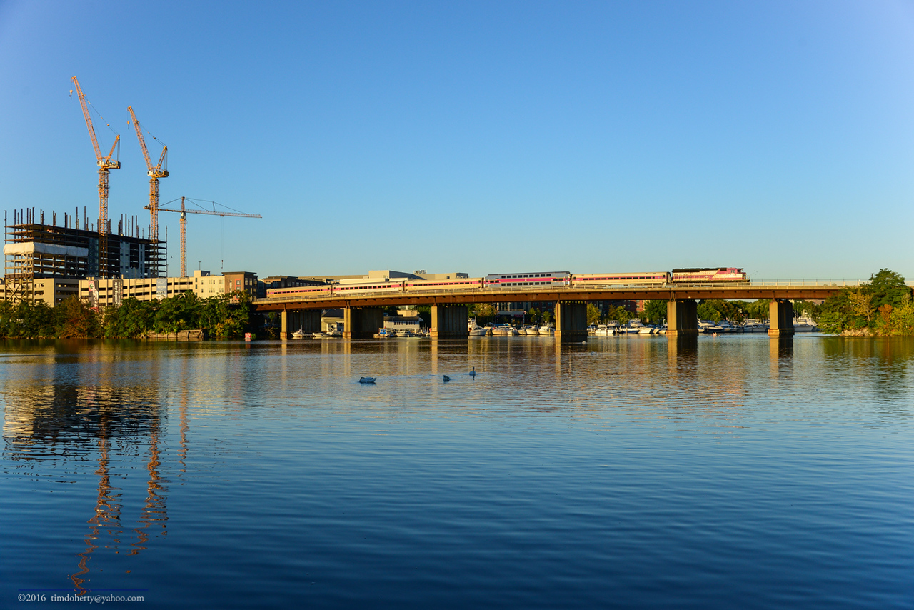 The first outbound train to Reading on Haverhill Line crosses the Mystic River Bridge between Somerville and Medford.