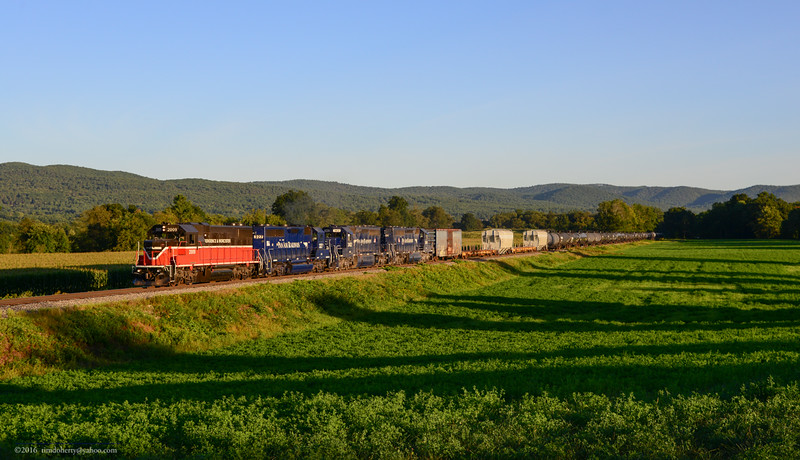 Leaving Massachusetts in the distance, Pan Am's East Deerfield to Bellows Falls train EDBF heads north on the NECR at Vernon, VT.