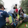 Team Rubicon members work together to cinch a simulated injured victim into a portable stretcher. Team Rubicon members from Region 9 participated in a three-day Wilderness First Aid/First Responder training at Beals Point in Folsom, Cali. The training taught TR members about providing aid when they come those who sustained injuries.