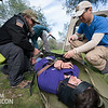 Team Rubicon member and  wilderness first aid associate instructor Patrick Mishler, left, helps Tim Tran how cinch Christian Velasquez into a portable stretcher. Team Rubicon members from Region 9 participated in a three-day Wilderness First Aid/First Responder training at Beals Point in Folsom, Cali. The training taught TR members about providing aid when they come those who sustained injuries.