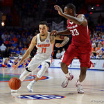 Univeristy of Florida Gators guard Chris Chiozza driving past Univeristy of Arkansas Razorbacks forward Moses Kingsley during the second half as the Gators celebrate senior day defeating the University of Arkansas Razorbacks 78-65 in Exactech Arena at the Stephen C. O'Connell Center in Gainesville, Florida.  March 1st, 2017. Gator Country photo by David Bowie.