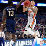 Univeristy of Florida Gators guard Chris Chiozza scores over East Tennessee State University Buccaneers guard A.J. Merriweather during the second half as the Gators advance to the second round of 2017 NCAA Tournament with a win over the  East Tennessee State Buccaneers 80-65.  March 16th, 2017.  Gator Country photo by David Bowie.