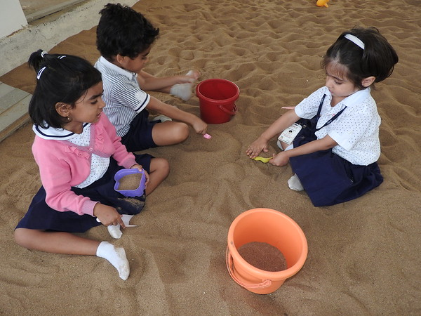 ENJOYING PLAYING IN SANDPIT