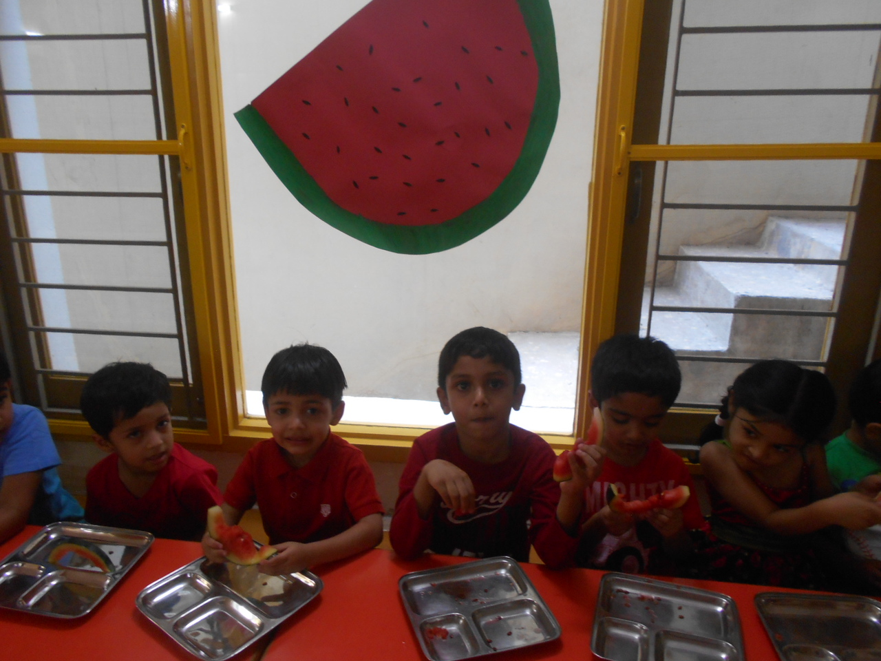 CHILDREN EATING WATERMELON DURING WATERMELON PARTY