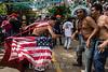 Nicaragua - Managua 01/08/2016 Millares de promesantes acudieron a la tradicional traida de Santo Domingo de Guzman de las Sierritas hacia la capital . Durante el recorrido de la diminuta imagen los socorristas de la CruzRoja brindaron atencion de primeros auxilios a varios promesantes y la Policia Nacional garantizo el orden durante todo el trayecto sin hechos que lamentar / The Santo Domingo de Guzman festival in Managua, Nicaragua , is filled with rituals and dancing, feasting, celebrations and worshipping - Thousands of people give thanks to Santo Domingo and ask for blessings during the 10-day festival - men covered in motor oil  / Nikaragua : Fest des Santo Domingo de Guzman , Schutzheiliger von Managua - Mann mit amerikanischer Flagge © Oscar Navarrete/LATINPHOTO.org