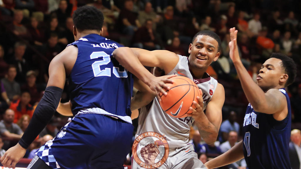 Nickeil Alexander-Walker moves between a pair of defenders with the ball. (Mark Umansky/TheKeyPlay.com)