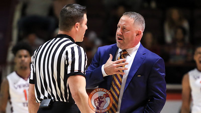 Hokies head coach Buzz Williams speaks with a referee in the opening minutes of the game after a foul call against Virginia Tech. (Mark Umansky/TheKeyPlay.com)