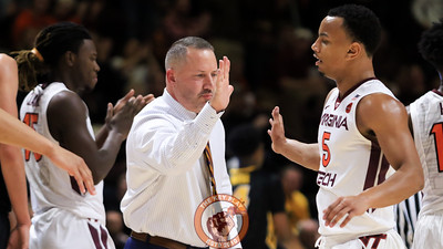 Head coach Buzz Williams high fives Justin Robinson as the Hokies come off the court during a timeout. (Mark Umansky/TheKeyPlay.com)