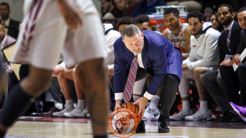 Head coach Buzz Williams bends down to collect a rolling loose ball during a stoppage in play. (Mark Umansky/TheKeyPlay.com)