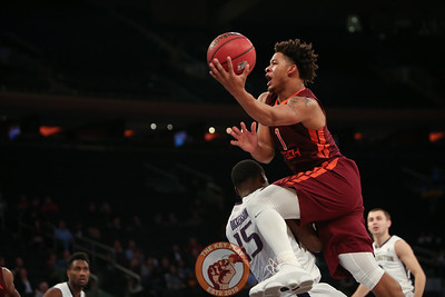 Virginia Tech's guard Tyrie Jackson (1) drives over Washington's forward Noah Dickerson (15) in Madison Square Garden, Nov. 17, 2017. Virginia Tech won the game 103-79.