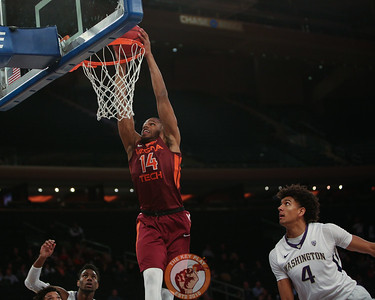 Virginia Tech's forward P.J. Horne (14) dunks past Washington's guard Matisse Thybulle (4) in Madison Square Garden, Nov. 17, 2017. Virginia Tech won the game 103-79.
