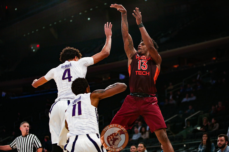 Virginia Tech's guard Ahmed Hill (13) shoots over Washington's guard Matisse Thybulle (4) and forward Nahziah Carter (11) in Madison Square Garden, Nov. 17, 2017. Virginia Tech won the game 103-79.