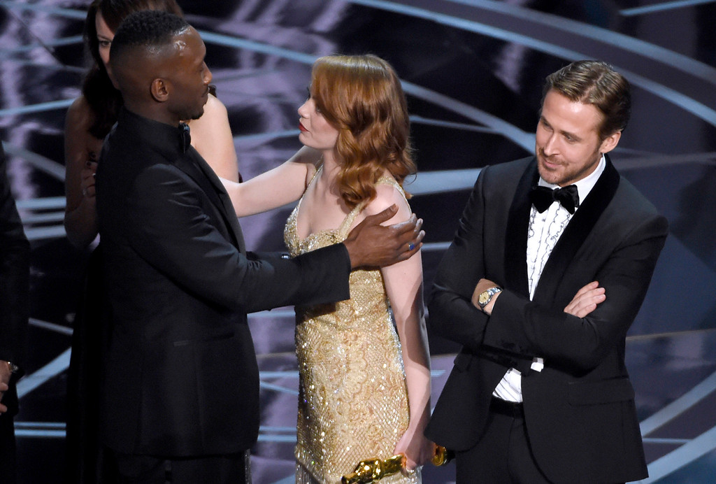 """. Ryan Gosling, right, stands with his arms folded as Emma Stone, center, congratulates Mahershala Ali, for winning the award for best picture for \""""Moonlight\"""" at the Oscars on Sunday, Feb. 26, 2017, at the Dolby Theatre in Los Angeles. It was originally announced mistakenly that \""""La La Land\"""" was the winner. (Photo by Chris Pizzello/Invision/AP)"""
