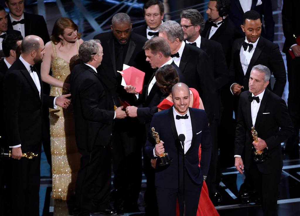 """. Fred Berger, producer of \""""La La Land,\"""" foreground center, gives his acceptance speech as members of PricewaterhouseCoopers, Brian Cullinan, holding red envelope, and Martha L. Ruiz, in red dress, and a stage manager discuss the best picture announcement error among the cast at the Oscars on Sunday, Feb. 26, 2017, at the Dolby Theatre in Los Angeles. The actual winner of best picture went to \""""Moonlight.\"""" (Photo by Chris Pizzello/Invision/AP)"""