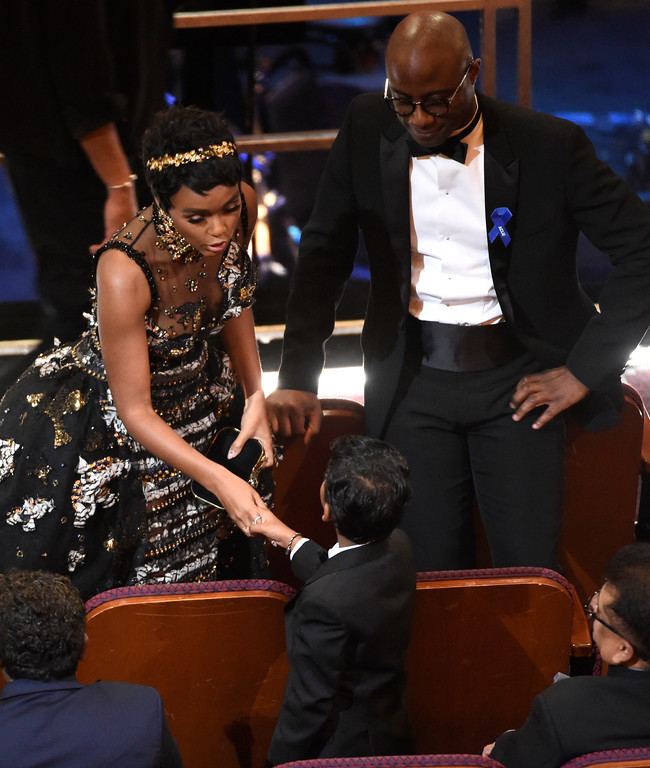 """. Janelle Monae, left, shakes hands with \""""Lion\"""" actor Sunny Pawar as \""""Moonlight\"""" director Barry Jenkins, right, looks on at the Oscars on Sunday, Feb. 26, 2017, at the Dolby Theatre in Los Angeles. (Photo by Chris Pizzello/Invision/AP)"""