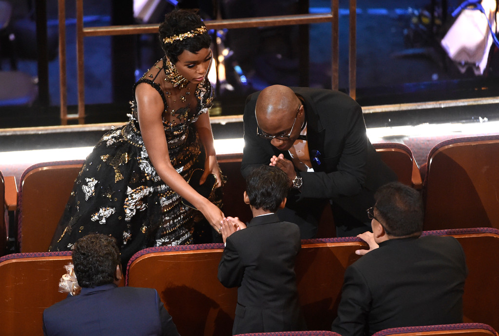""". Janelle Monae, left,  shakes hands with \""""Lion\"""" actor Sunny Pawar as \""""Moonlight\"""" director Barry Jenkins gestures to Pawar in the audience at the Oscars on Sunday, Feb. 26, 2017, at the Dolby Theatre in Los Angeles. (Photo by Chris Pizzello/Invision/AP)"""