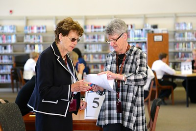 Interviewer Judy Bennett (right) discusses evaluation forms with Dr. Carol Ann Hackley.