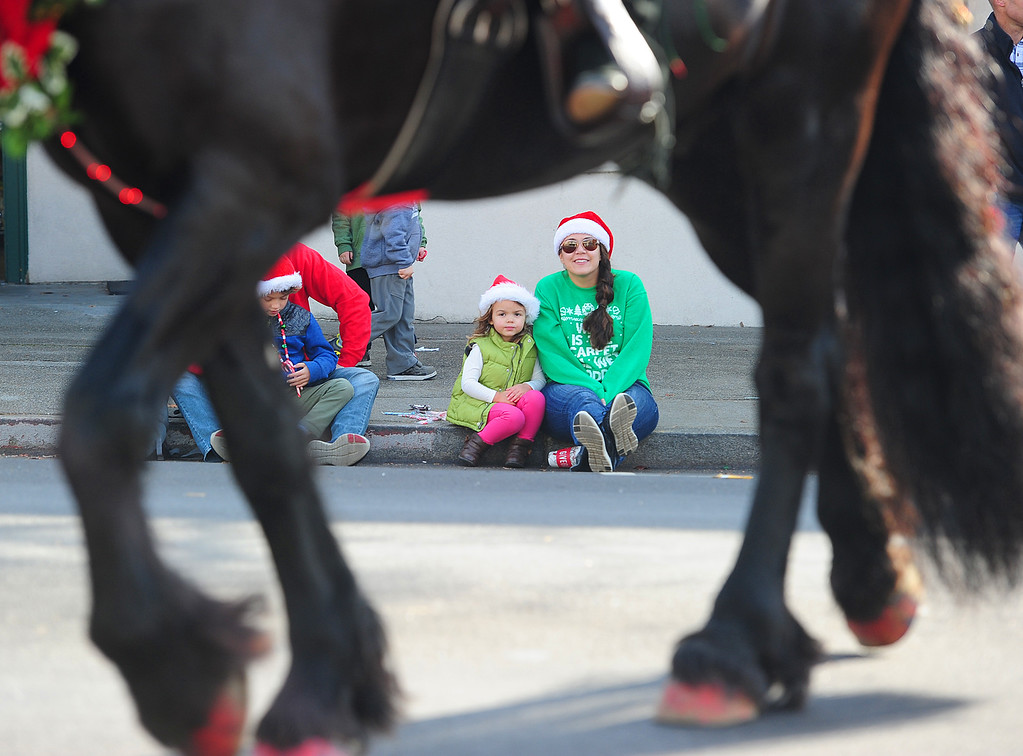 . BENICIA, CA- DEC. 9, Ana Anderson with her daughte June, 3, watch as horses pass during the Benicia Holiday Parade down First Street on Saturday. (CHRIS RILEY/Times-Herald)