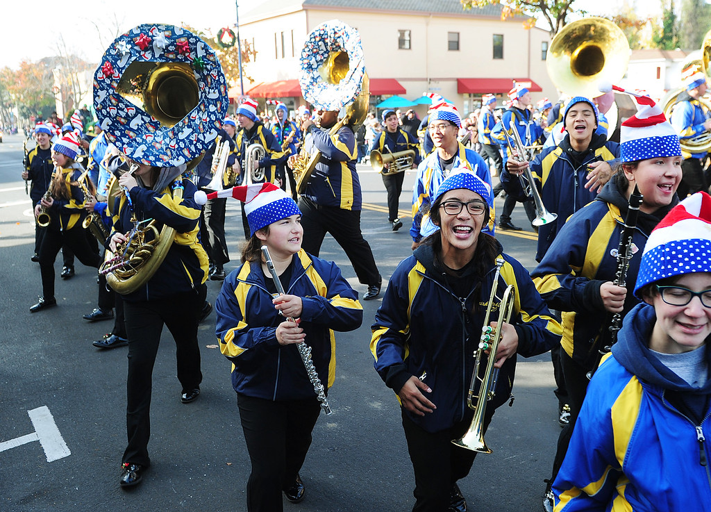 . BENICIA, CA- DEC. 9, The Benicia High School marching band runs into the crowd as they sing \'We Wish You a Merry Christmas\' during the Benicia Holiday Parade down First Street on Saturday. (CHRIS RILEY/Times-Herald)