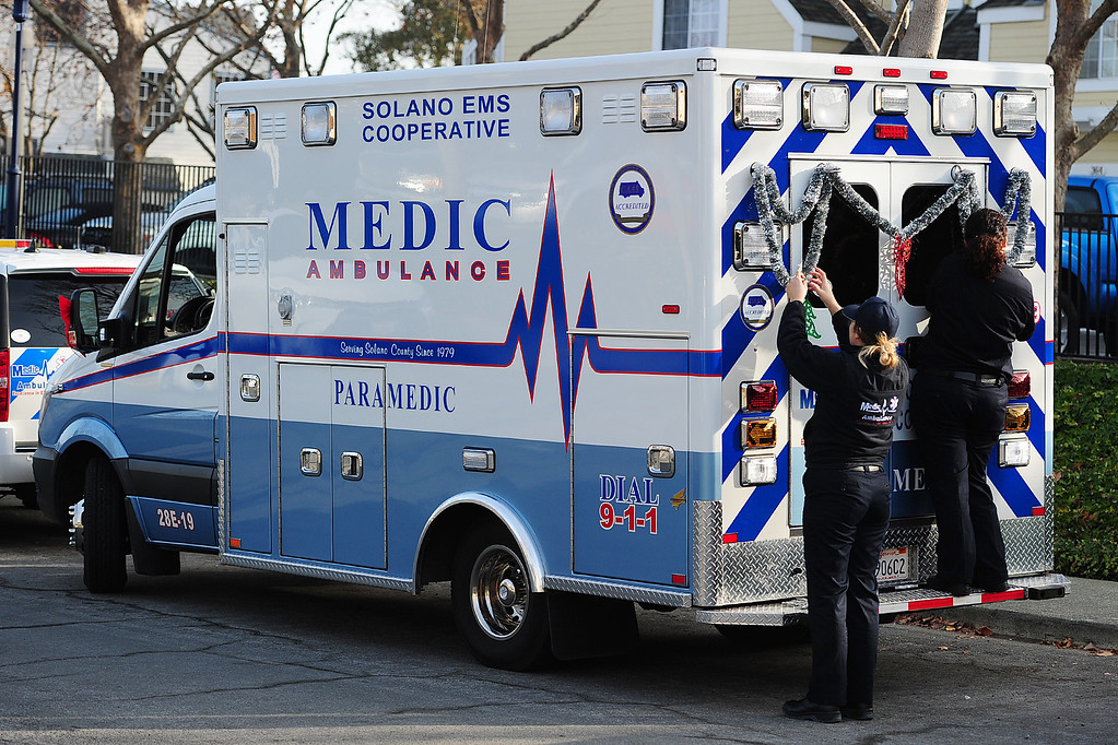 . BENICIA, CA- DEC. 9, Paramedics with Medic Ambulance decorate their rig before the start of the Benicia Holiday Parade down First Street on Saturday. (CHRIS RILEY/Times-Herald)