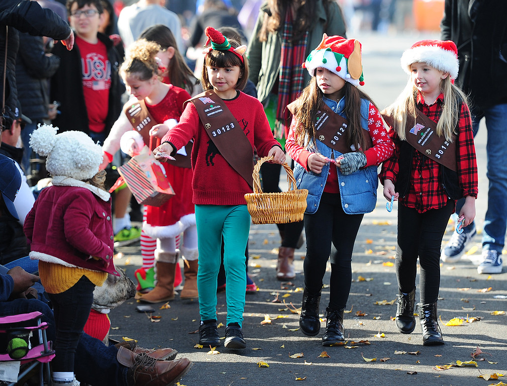 . BENICIA, CA- DEC. 9, Girls scouts with Troop 30123 pass out candy canes during the Benicia Holiday Parade down First Street on Saturday. (CHRIS RILEY/Times-Herald)