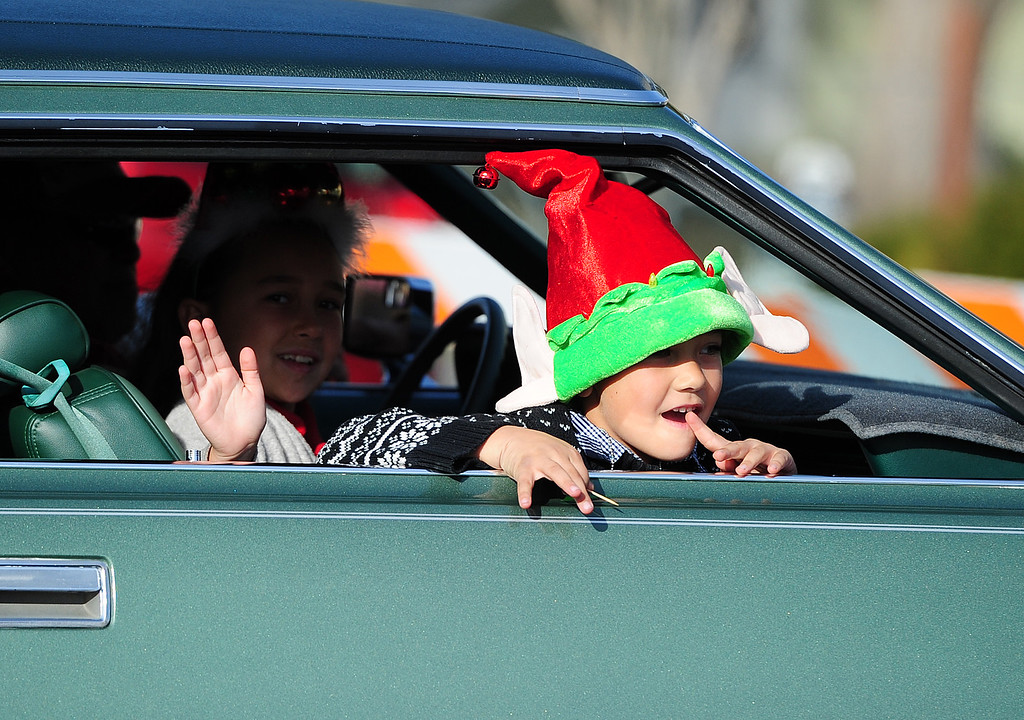 . BENICIA, CA- DEC. 9, A young rider waves to the crowd during the Benicia Holiday Parade down First Street on Saturday. (CHRIS RILEY/Times-Herald)