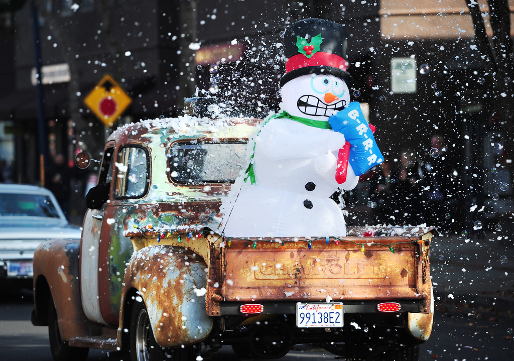 . (CHRIS RILEY �Times-Herald) A inflatable snowman appears to be cold as bubbles and artificial snow fall over the back a classic Chevy truck driving in the Benicia Christmas parade with the Boyz Under the Hood car club down First Street on Saturday.