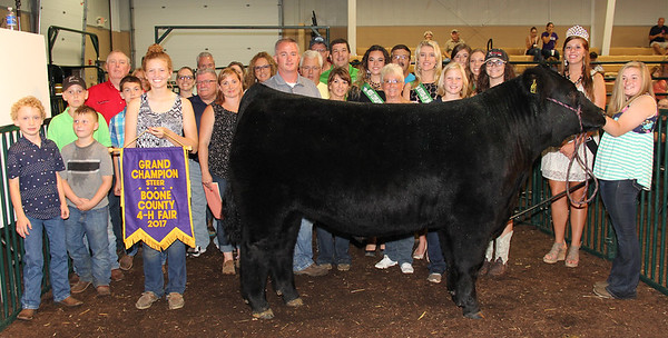 Rod Rose The Lebanon Reporter<br /> A GRAND REWARD: Nola Dickerson stands with her grand champion steer, while family, friends and representatives of buyers join her after she received $4,800 for the animal at Thursday's Boone County 4-H Fair auction. Buyers included