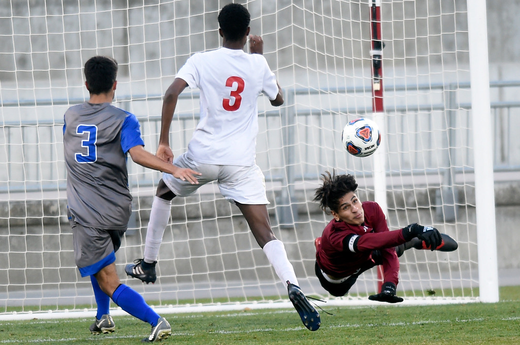 . Broomfield High School goalkeeper Jose Ogaz makes a save on a goal attempt by Zion Wagoner during the CHSAA 5A State Championship game against Denver East High School on Saturday at Dick\'s Sporting Goods Park in Commerce City. Broomfield won the game 1-0. For more photos go to BoCoPreps.com Jeremy Papasso/ Staff Photographer/ Nov. 11, 2017