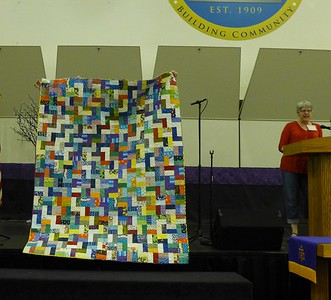 Lynda Patriarche showing a quilt made by members of Scrap Fever and quilted by John Putnam.  Quilt is being donated to Helping Hands Respite Center.