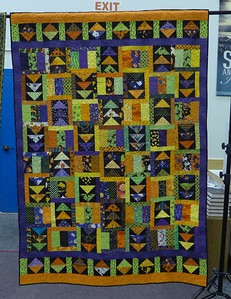 Raffle Quilt by Scrap Fever.  Pieced by members of Scrap Fever, top assembled by Vernita Dailey and machine quilted by John Putnam.  Quilt size 56 X 80