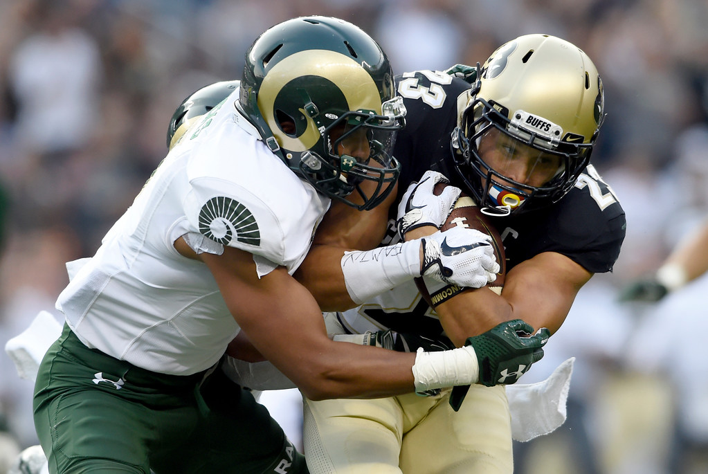 . University of Colorado\'s Phillip Lindsay is tackled by Jamal Hicks during the Rocky Mountain Showdown against Colorado State University on Friday at Sports Authority Field in Denver. More photos: Buffzone.com Jeremy Papasso/ Staff Photographer/ Sept. 1, 2017