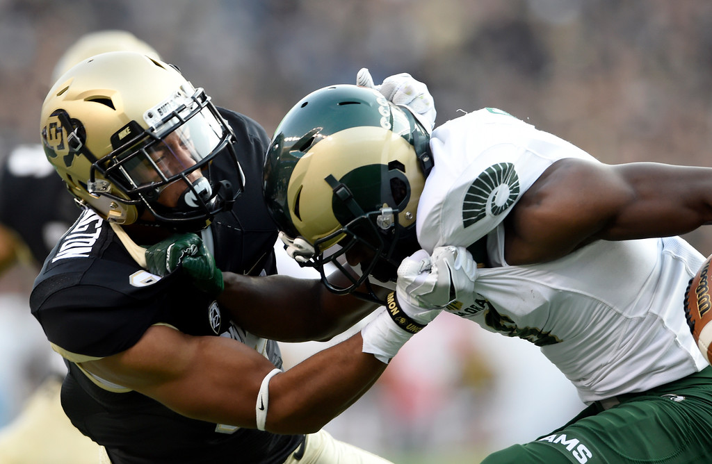 . University of Colorado\'s Evan Worthington tackles Dalyn Dawkins during the Rocky Mountain Showdown against Colorado State University on Friday at Sports Authority Field in Denver. More photos: Buffzone.com Jeremy Papasso/ Staff Photographer/ Sept. 1, 2017