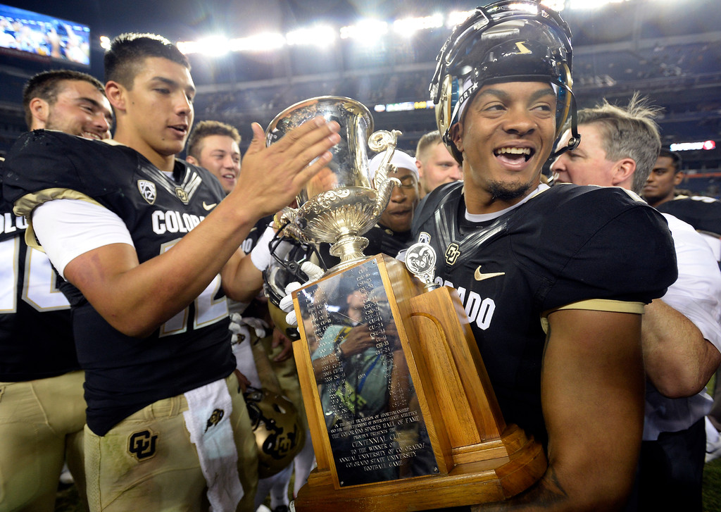 . Steven Montez, left, and Shay Fileds, hold the Centennial Cup after beating CSU in the Rocky Mountain Showdown in Denver.  Cliff Grassmick / Staff Photographer/ September 1, 2017